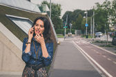 Pretty girl talking on phone in the city streets — Stok fotoğraf