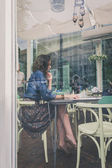 Pretty girl sitting in restaurant framed through the glass of a window — Stok fotoğraf