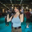 Постер, плакат: Lara Croft cosplayer posing at Games Week 2014 in Milan Italy
