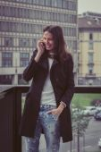 Pretty girl talking on phone in the city streets — ストック写真