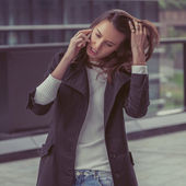 Pretty girl talking on phone in the city streets — Stock Photo