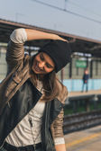 Pretty girl listening to music in a metro station — Stock Photo