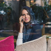 Beautiful girl talking on phone behind a window — ストック写真