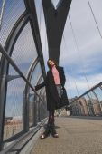 Beautiful young brunette posing on a bridge — Stock Photo