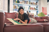 Beautiful young brunette reading book in a bookstore — Stock fotografie