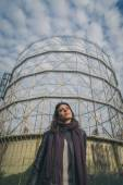 Beautiful young brunette posing in front of a gasometer — Stock Photo