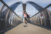 Beautiful young brunette jumping on a bridge — Stock Photo