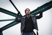 Punk guy standing on a bridge — Stock Photo