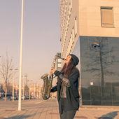 Beautiful young woman playing tenor saxophone — Stock Photo