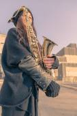 Beautiful young woman with her saxophone — Stock Photo