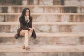 Beautiful young woman sitting on concrete steps — Stock Photo