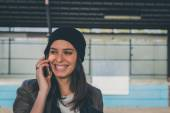Pretty girl talking on phone in a metro station — Stock Photo