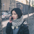 Young beautiful Chinese girl talking on phone in the city streets — Stock Photo #65093541