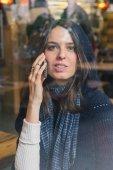 Beautiful girl talking on phone behind a window — Foto de Stock