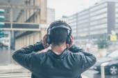 Back view of a young man with headphones posing in the city stre — Stock fotografie