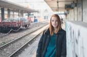 Beautiful girl posing in a railroad station — Stock Photo