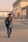 Beautiful young woman playing tenor saxophone — Stock Photo