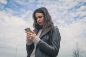 Beautiful young brunette texting in the city streets — Stock Photo