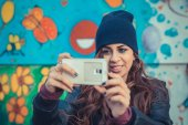 Beautiful girl taking a selfie in the city streets — Stock Photo