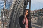Beautiful young brunette posing on a bridge — Stock Photo