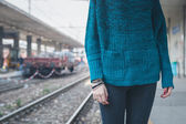 Detail of a girl posing in a railroad station — Stock Photo