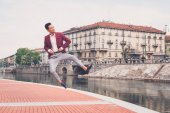Handsome Asian model jumping by an artificial basin — Stock Photo