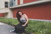 Beautiful curvy girl sitting in the grass — Stock Photo