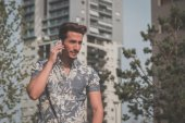 Young handsome man talking on phone in the street — Stock Photo
