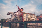 Handsome Asian model jumping in the city streets — Stock Photo