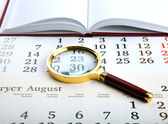 Magnifier on the diary — Stock Photo