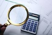 Man considers the budget through a magnifying glass — Stock Photo