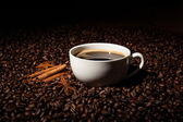 Still-life with a cup of black coffee and roasted coffee beans — Stock Photo