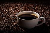 Stillleben mit einer Tasse schwarzen Kaffee und geröstete Kaffeebohnen — Stockfoto
