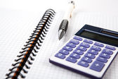Pen on a notebook into a cell and calculator — Stock Photo