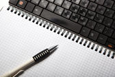 Pen on a notebook into a cell and keyboard — Stock Photo