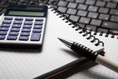 Pen with calculator on a notebook and keyboard — Stock Photo
