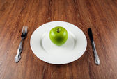 Table appointments and the fresh green apple on a white plate — Stock Photo