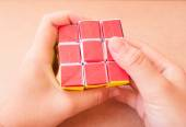 Play puzzle rubik cube make by paper in han — Stock Photo
