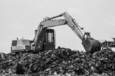 Mountain of garbage with working backhoe  — Stock Photo