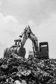 Mountain of garbage with working backhoe , monochromatic  — Stock Photo