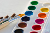 Colorful new watercolor paint pan set and brushes — Stock Photo