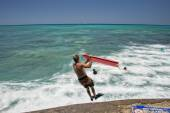 Man jumping from pier with body surf — Stock Photo