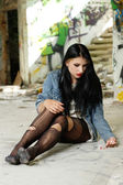 Girl addict in torn tights and with pills sitting on the floor — Stock Photo
