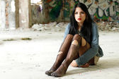 Girl in torn tights sitting on the floor — Stock Photo
