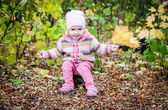 Happy toddler girl gathers leaves — Stock Photo