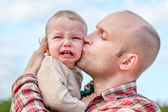 Caring father calms toddler son outdoors  — 图库照片
