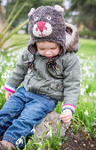 Cute toddler boy trying to disrupt the snowdrop — Stock Photo