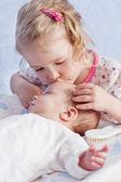 Cute Toddler sister kisses newborn — Stock Photo