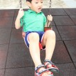 Asian boy playing swing in the park — Stock Photo #77722670