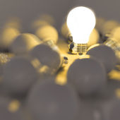 Growing light bulb standing out from the unlit incandescent bulb — Stock Photo